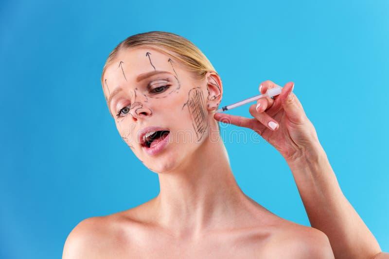 Το πρόσωπο ενός κοριτσιού με το ομαλό δέρμα χωρίς ρυτίδες κάνει τους πυροβολισμούς ομορφιάς Σύριγγα δίπλα στο πρόσωπο, σαλόνι φρο στοκ φωτογραφία