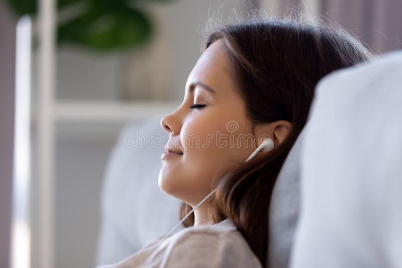 Το πρόσωπο κινηματογραφήσεων σε πρώτο πλάνο πλάγιας όψης της γυναίκας που φορά τα ακουστικά απολαμβάνει τη μουσική στοκ φωτογραφίες με δικαίωμα ελεύθερης χρήσης