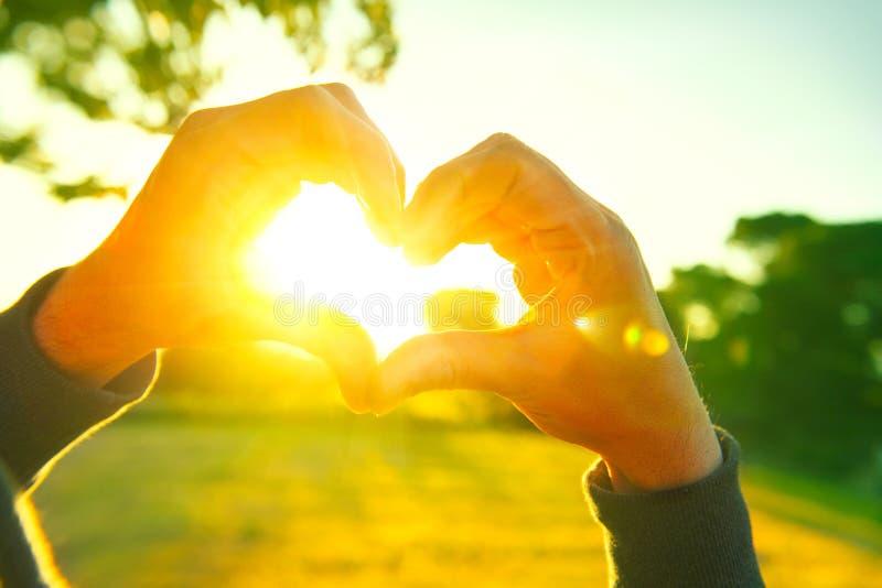 Το πρόσωπο που κατασκευάζει την καρδιά με παραδίδει το υπόβαθρο ηλιοβασιλέματος φύσης στοκ φωτογραφία με δικαίωμα ελεύθερης χρήσης