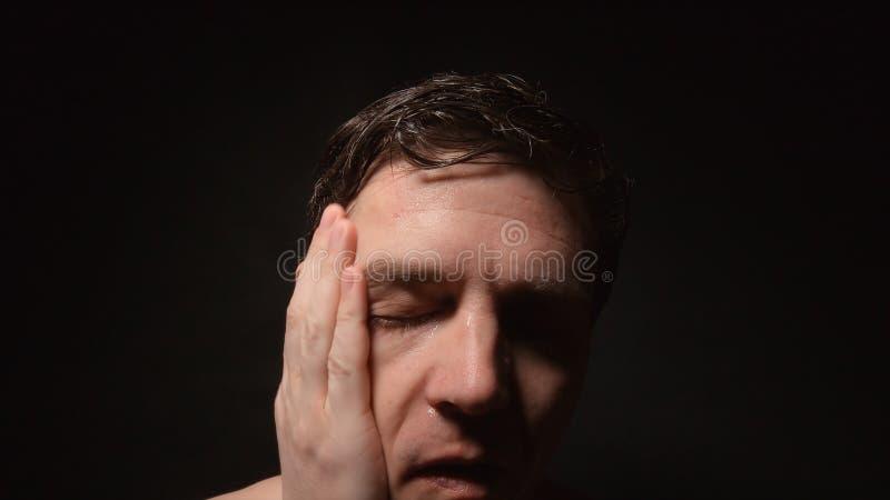 Το πρόσωπο του ιδρώνοντας ατόμου σκούπισε το υγρό πρόσωπό του παραδίδει κοντά το σκοτεινό δωμάτιο στοκ εικόνες