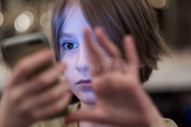 Το πρόσωπο του παιδιού, που φωτίζεται από την οθόνη του τηλεφώνου στοκ εικόνες με δικαίωμα ελεύθερης χρήσης