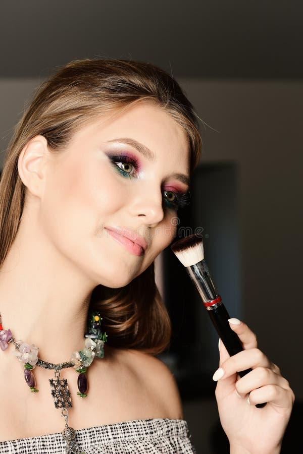 Το πρότυπο με τη βούρτσα makeup, κλείνει επάνω Κορίτσι που φορά το ζωηρόχρωμα makeup και το περιδέραιο Κυρία με την ανοικτή μπλού στοκ φωτογραφία με δικαίωμα ελεύθερης χρήσης