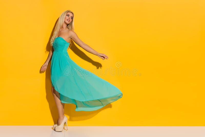 Το πρότυπο μόδας θέτει στο τυρκουάζ φόρεμα και τα υψηλά τακούνια στοκ εικόνα με δικαίωμα ελεύθερης χρήσης