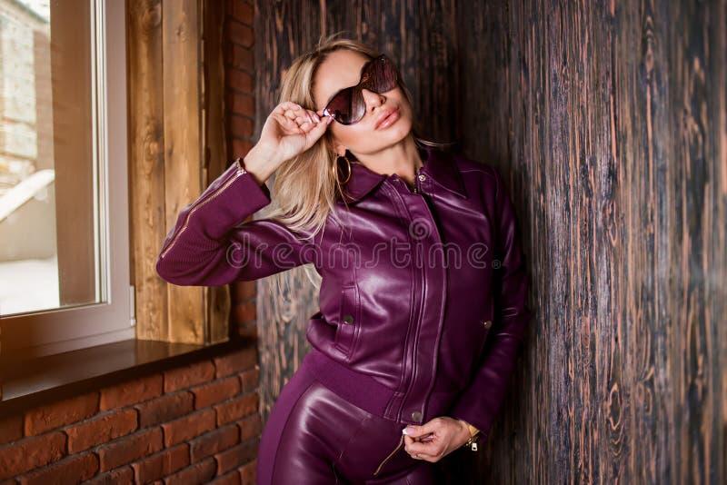 Το πρότυπο μόδας στα γυαλιά ηλίου, πορφυρό σακάκι δέρματος, εσώρουχα δέρματος που θέτει με παραδίδει την τσέπη κοντά στον ξύλινο  στοκ εικόνες