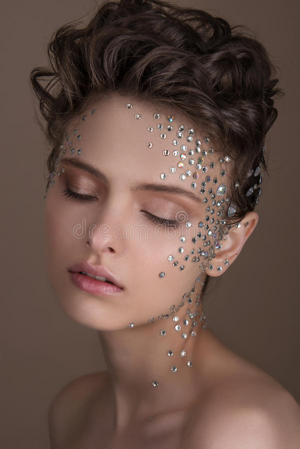 Το πρότυπο μόδας με το φωτεινό makeup και ζωηρόχρωμος ακτινοβολεί και σπινθηρίσματα στο πρόσωπο και το σώμα της στοκ εικόνες με δικαίωμα ελεύθερης χρήσης