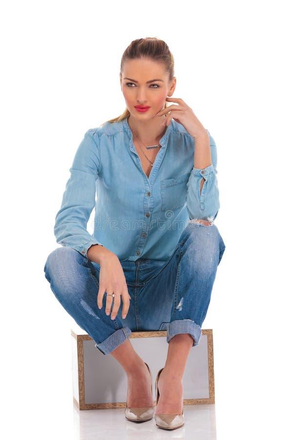 Το πρότυπο στο τζιν θέτει καθισμένος στο υπόβαθρο στούντιο με το χέρι στο kne στοκ εικόνα με δικαίωμα ελεύθερης χρήσης
