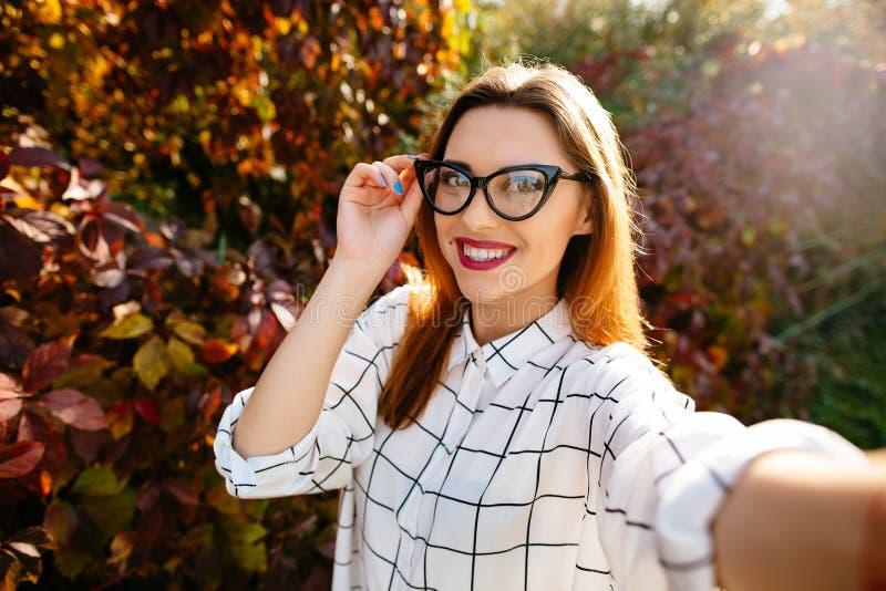 Το πρότυπο Gougeus παίρνει selfie κρατώντας τα γυαλιά της με ένα χέρι στοκ φωτογραφίες με δικαίωμα ελεύθερης χρήσης
