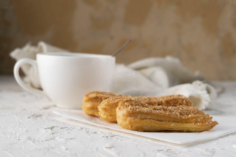 το πρόχειρο φαγητό πρωινού με τον καφέ και κρεμώδες ECLAIR σε έναν πίνακα με το άσπρο τραπεζομάντιλο, επιχείρηση προγευματίζουν στοκ φωτογραφία με δικαίωμα ελεύθερης χρήσης