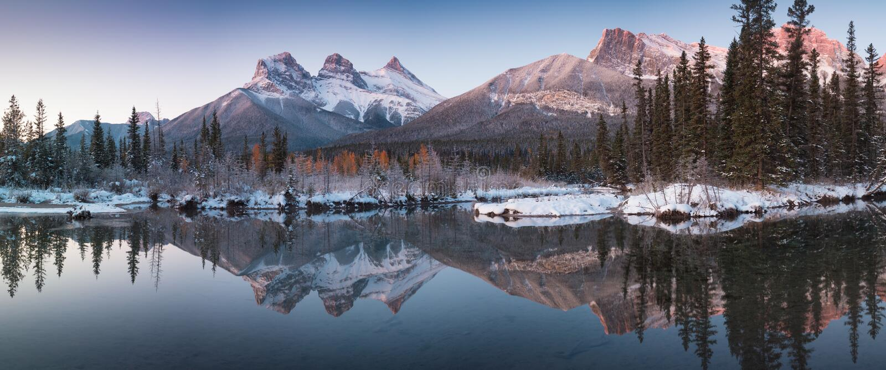 Το πρώτο χιόνι σχεδόν τέλεια αντανάκλαση των τριών αδελφών κορυφώνεται στον ποταμό Μπόου Canmore στο Banff National Park, Καναδάς στοκ εικόνες