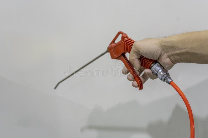 Το πυροβόλο όπλο χτυπήματος αέρα της πορτοκαλιάς λαβής χρήσης κρατά στοκ φωτογραφίες με δικαίωμα ελεύθερης χρήσης