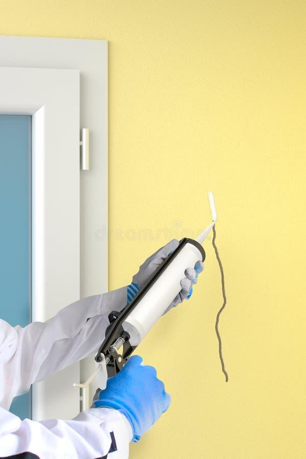 Το πυροβόλο όπλο στεγανωτικής ουσίας σιλικόνης γεμίζει τη ρωγμή στον τοίχο στοκ φωτογραφία με δικαίωμα ελεύθερης χρήσης