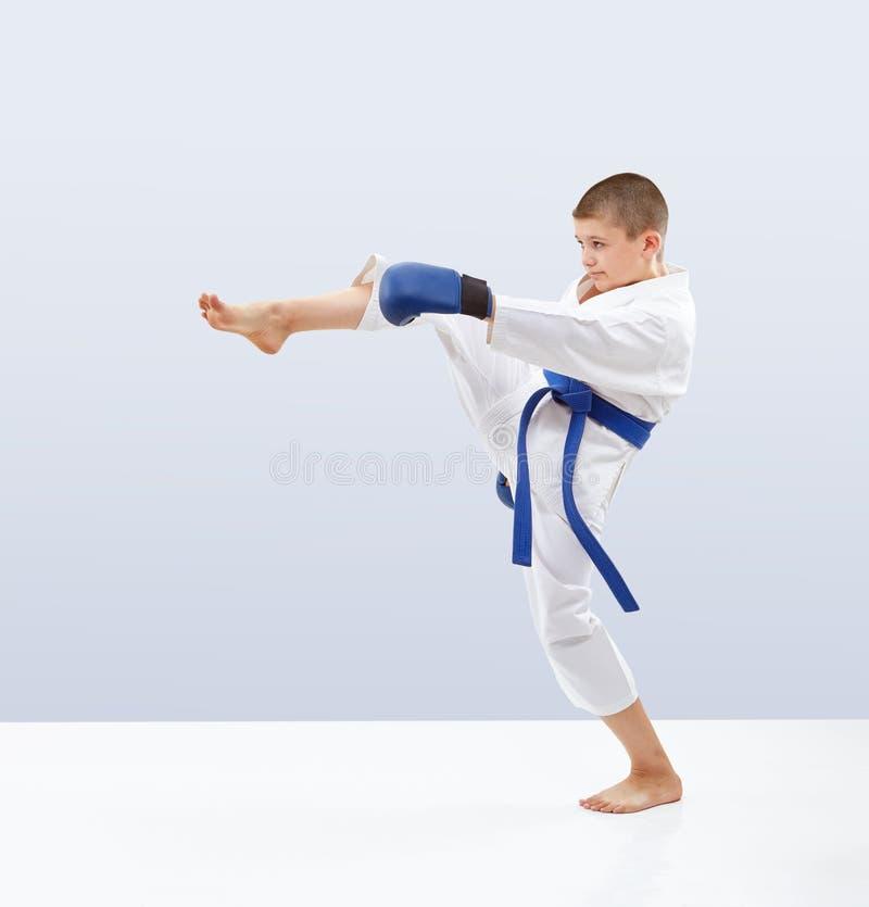 Το πόδι χτυπήματος μπροστινό κτυπά τον αθλητή στο karategi στοκ εικόνα