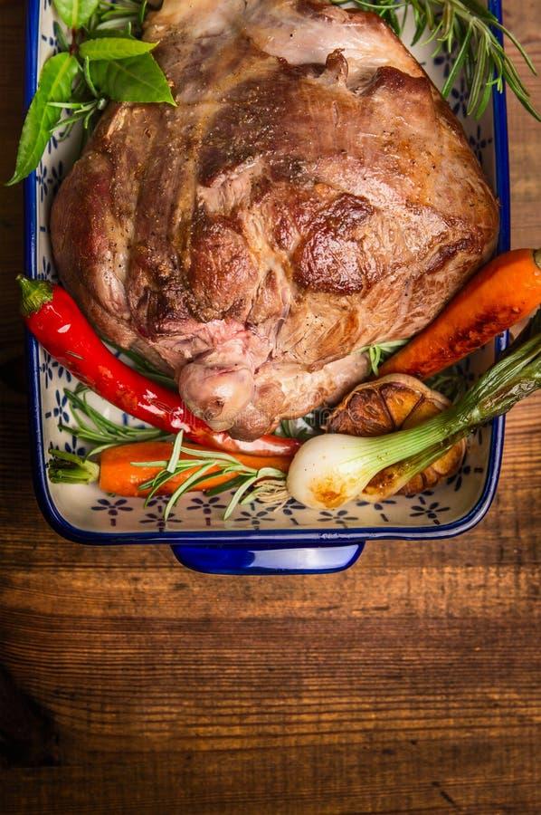 Το πόδι ψητού του αρνιού με τα λαχανικά και τα χορτάρια casserole κυλούν στο αγροτικό ξύλινο υπόβαθρο, τοπ άποψη στοκ φωτογραφίες