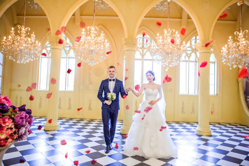 Το πλήρες μήκος της κομψής εκμετάλλευσης γαμήλιων ζευγών παραδίδει την εκκλησία στοκ φωτογραφίες