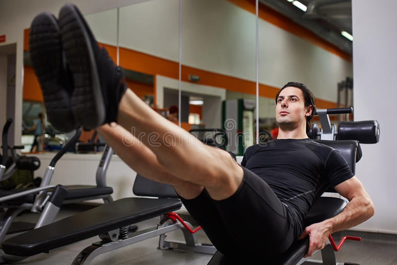 Το πλήρες πορτρέτο μήκους του μυϊκού ατόμου κατασκευής κάνοντας τα πόδια πιέζει την άσκηση στο κέντρο ικανότητας στοκ φωτογραφία με δικαίωμα ελεύθερης χρήσης