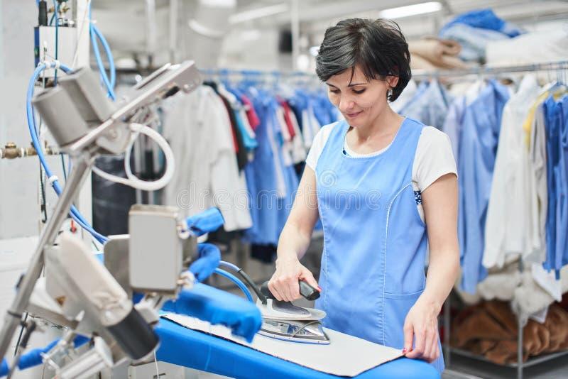 Το πλυντήριο εργαζομένων που σιδερώνεται το σίδηρο ντύνει ξηρό στοκ εικόνες