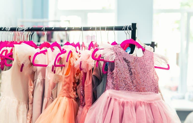 Το ράφι με πολλούς όμορφες διακοπές ντύνει για τα κορίτσια στις κρεμάστρες στην αίθουσα εκθέσεως μόδας παιδιών εσωτερική Στούντιο στοκ εικόνα