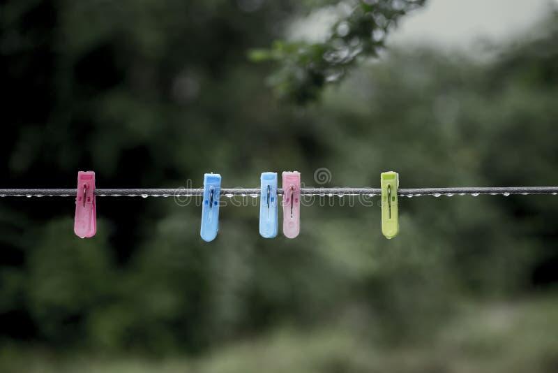 Το ραβδί νερού βροχής στο clothespin και η σκοινί για άπλωμα φαίνονται σύγκρουση επειδή το clothespin και η σκοινί για άπλωμα χρη στοκ φωτογραφίες