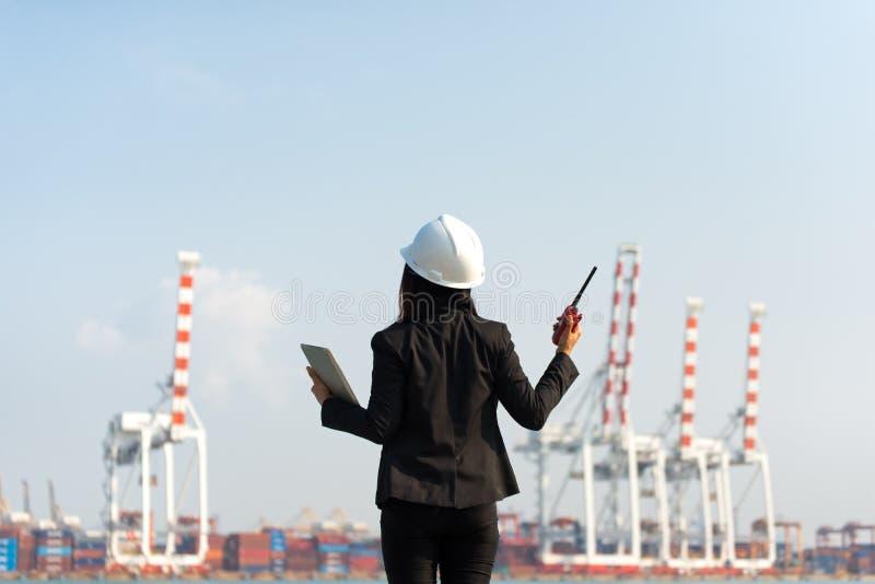 Το ραδιόφωνο εκμετάλλευσης μηχανικών γυναικών και εργασία με το σκάφος φορτίου φορτίου εμπορευματοκιβωτίων στο ναυπηγείο στο σούρ στοκ φωτογραφίες