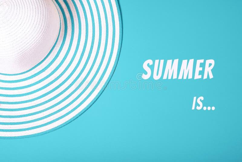 """Το ριγωτό καπέλο αχύρου στο γαλαζοπράσινο σμαραγδένιο υπόβαθρο χρώματος χρώματος με την επιγραφή """"καλοκαίρι είναι """" r r στοκ φωτογραφία"""