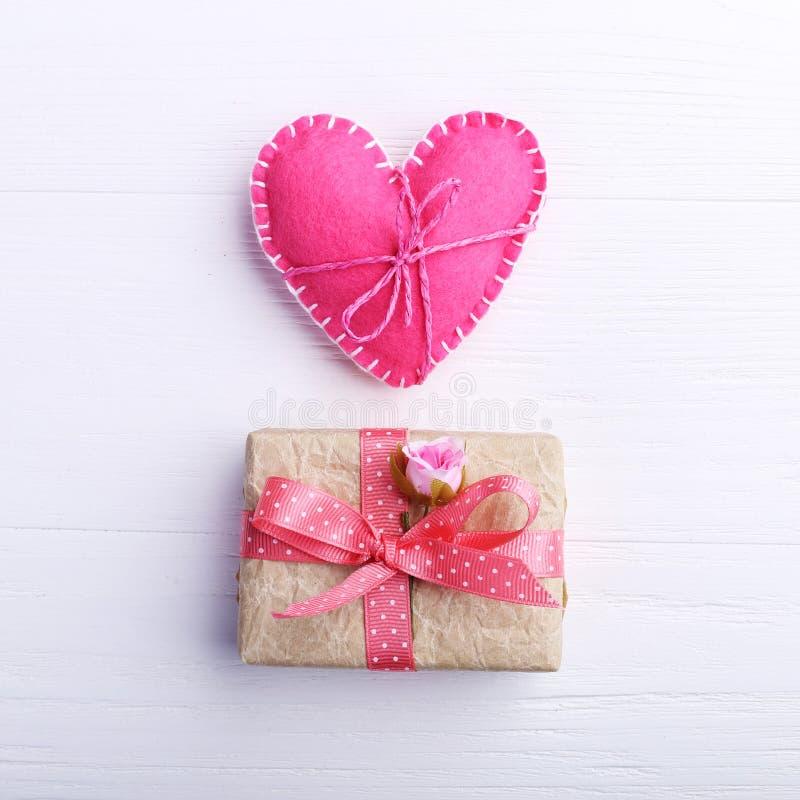 Το ροζ αισθάνθηκε την καρδιά και το χειροποίητο δώρο σε έναν άσπρο ξύλινο πίνακα, έννοια, έμβλημα, διάστημα αντιγράφων στοκ εικόνα με δικαίωμα ελεύθερης χρήσης
