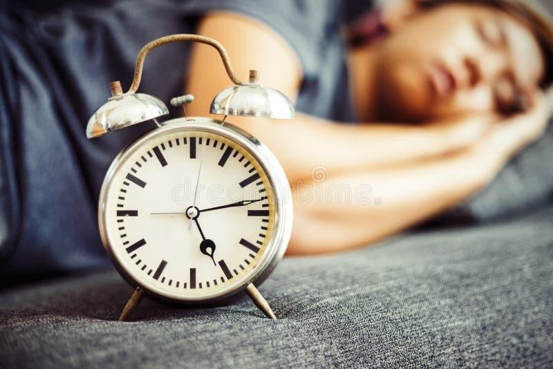 Το ρολόι είναι στο κρεβάτι κοντά στον ύπνο γυναικών στοκ φωτογραφία με δικαίωμα ελεύθερης χρήσης