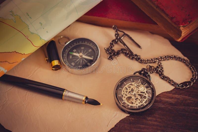 Το ρολόι τσεπών με τα παλαιά βιβλία και η μάνδρα με το έγγραφο χαρτογραφούν στον πίνακα στοκ εικόνες