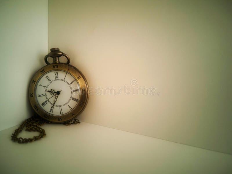 Το ρολόι φέρνει μια παλαιά τσάντα που τοποθετείται σε ένα άσπρο υπόβαθρο It' αντίκα του s στοκ εικόνες