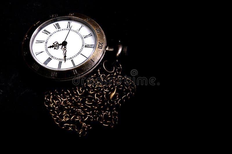 Το ρολόι φέρνει μια παλαιά τσάντα που τοποθετείται σε ένα μαύρο υπόβαθρο στοκ εικόνες με δικαίωμα ελεύθερης χρήσης