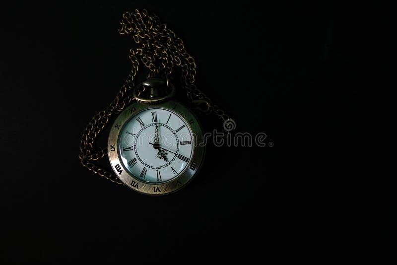 Το ρολόι φέρνει μια παλαιά τσάντα που τοποθετείται σε ένα μαύρο υπόβαθρο στοκ εικόνα