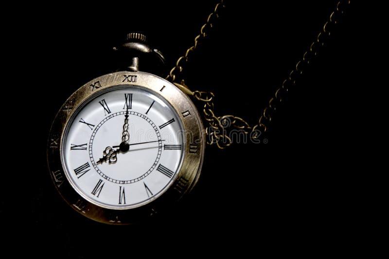 Το ρολόι φέρνει μια παλαιά τσάντα που τοποθετείται σε ένα μαύρο υπόβαθρο στοκ φωτογραφία