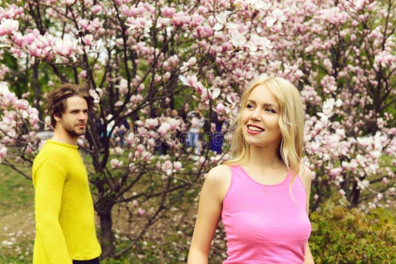 Το ρομαντικό ζεύγος ερωτευμένο την άνοιξη καλλιεργεί στο magnolia άνθισης στοκ φωτογραφία με δικαίωμα ελεύθερης χρήσης