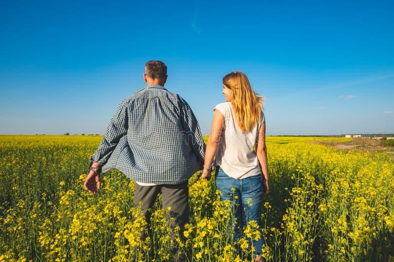 Το ρομαντικό ζεύγος περπατά μέσω του τομέα των κίτρινων λουλουδιών στοκ εικόνες
