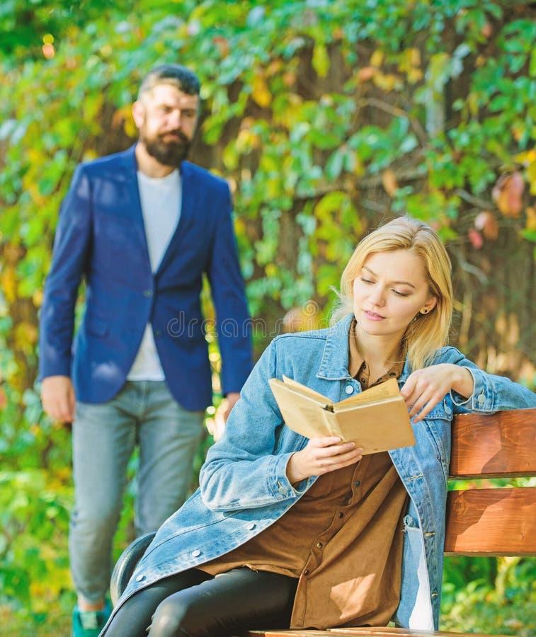 Το ρομαντικό ζεύγος συναντιέται στο πάρκο διαβασμένο γυναίκα intersting βιβλίο χαλαρώστε στον πάγκο πάρκων Λογοτεχνία χρόνος φθιν στοκ φωτογραφίες με δικαίωμα ελεύθερης χρήσης