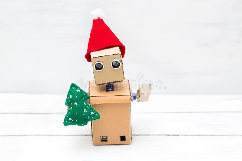 Το ρομπότ με παραδίδει ένα καπέλο Χριστουγέννων και ένα χριστουγεννιάτικο δέντρο στοκ εικόνα