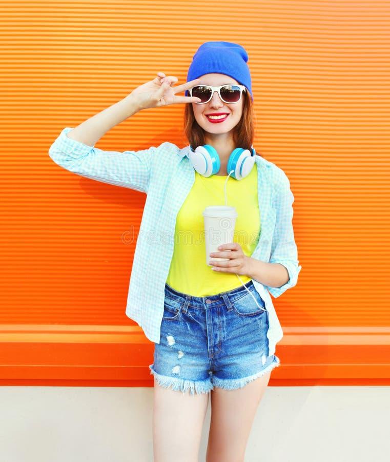 Το δροσερό κορίτσι μόδας αρκετά με το φλυτζάνι καφέ ακούει τη μουσική πέρα από το ζωηρόχρωμο πορτοκάλι στοκ φωτογραφία με δικαίωμα ελεύθερης χρήσης
