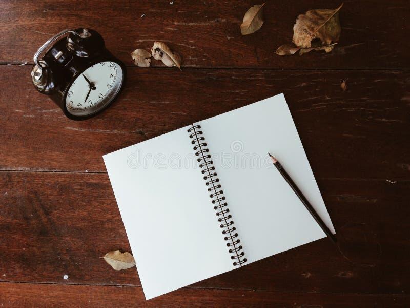 Το ρολόι, ξεραίνει τα φύλλα, το σημειωματάριο και το μολύβι στον ξύλινο πίνακα στοκ εικόνα