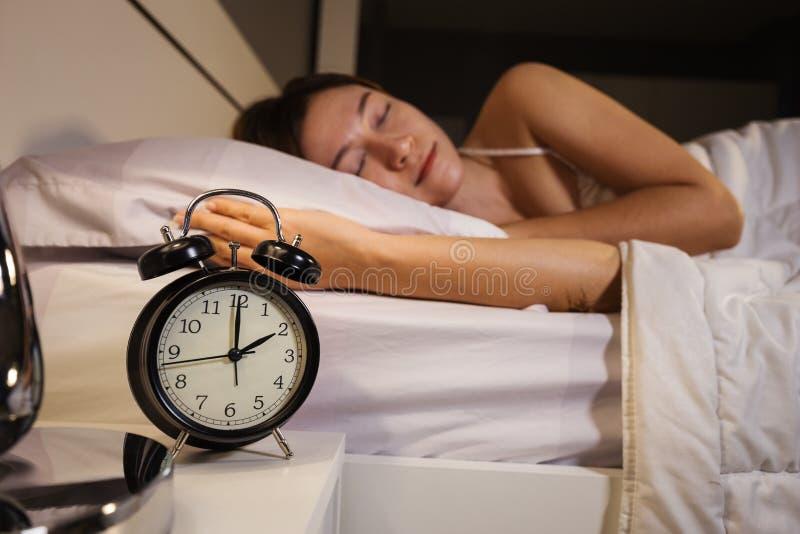 Το ρολόι παρουσιάζει ύπνο ρολογιών και γυναικών 2 Ο ` στο κρεβάτι στοκ φωτογραφία με δικαίωμα ελεύθερης χρήσης
