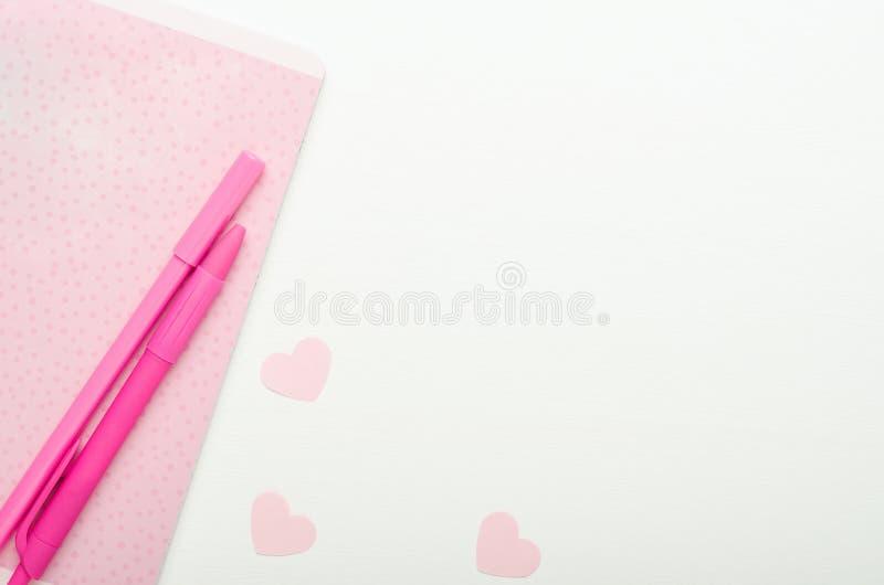 Το ρόδινες σημειωματάριο και οι μάνδρες σημείων Πόλκα, αποκόπτουν τις καρδιές σε ένα άσπρο ξύλινο υπόβαθρο Κορίτσια σχολικών γραφ στοκ εικόνες