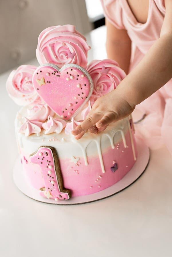 Το ρόδινο κέικ συντριβής στον εορτασμό των πρώτων γενεθλίων του κοριτσιού, κέικ σφουγγαριών, σπασμένο marshmallow, μωρό δίνει και στοκ εικόνες