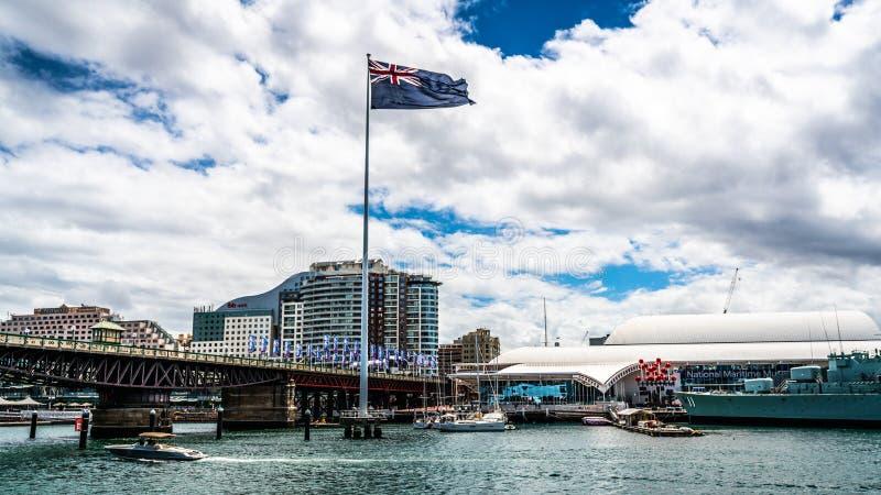 Το Σίδνεϊ ελλιμενίζει αγάπη μου το πανόραμα με τη γιγαντιαίες αυστραλιανές σημαία και τη γέφυρα Pyrmont με το συννεφιάζω καιρό σε στοκ φωτογραφία με δικαίωμα ελεύθερης χρήσης