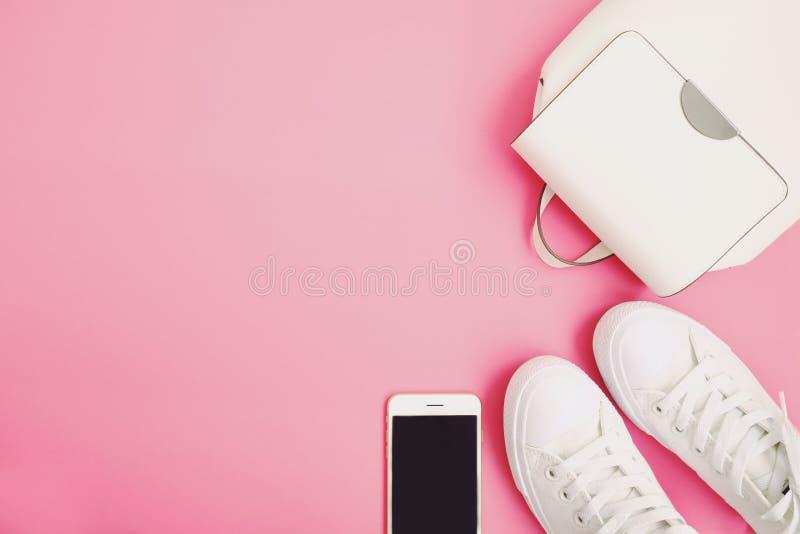 Το σακίδιο πλάτης εξαρτημάτων λευκών γυναικών, πάνινα παπούτσια, τηλεφωνά στο επίπεδο βάζει στο ρόδινο υπόβαθρο με το διάστημα κε στοκ φωτογραφίες
