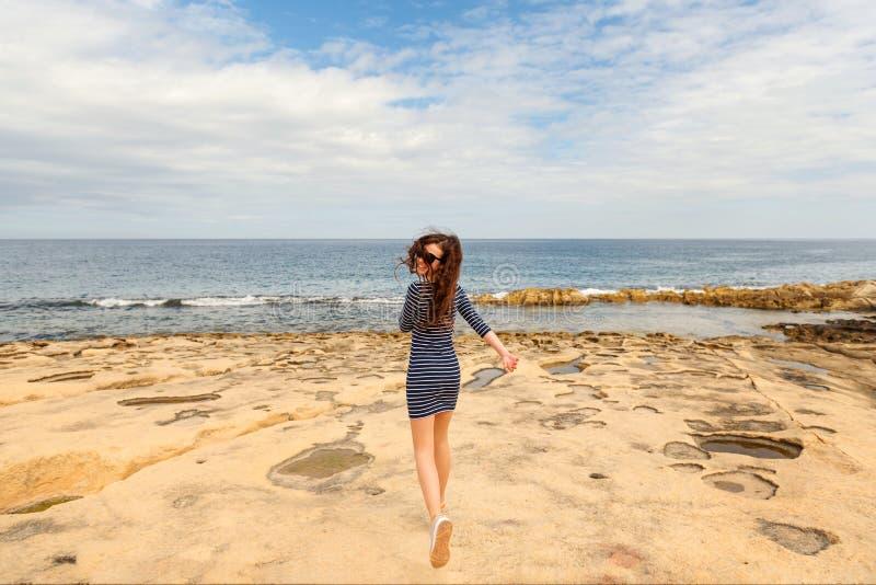 Το σγουρός-μαλλιαρό κορίτσι σε ένα ριγωτό φόρεμα και τα πάνινα παπούτσια τρέχει εύθυμα κατά μήκος της παραλίας λάβας της ωκεάνιας στοκ φωτογραφίες