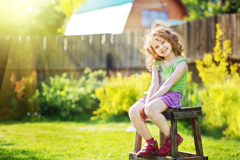 Το σγουρό κορίτσι κάθεται σε μια καρέκλα στο ναυπηγείο ενός εξοχικού σπιτιού στοκ εικόνα
