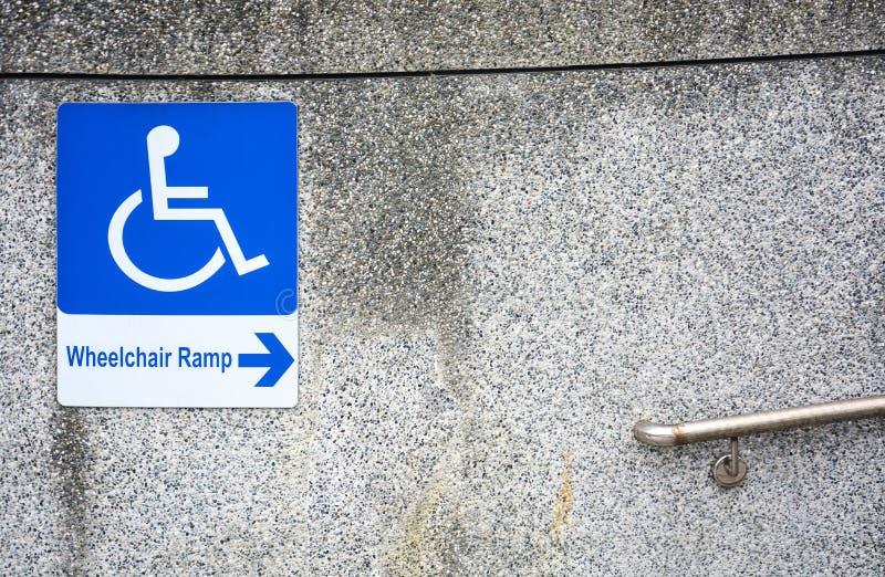 Το σημάδι κεκλιμένων ραμπών αναπηρικών καρεκλών για τα άτομα με ειδικές ανάγκες στη βρώμικη σύσταση τοίχων πετρών χαλικιών με το  στοκ φωτογραφία με δικαίωμα ελεύθερης χρήσης
