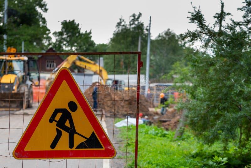 Το σημάδι οδικών εργασιών επάνω το υπόβαθρο των εργαζομένων και του εξοπλισμού κατασκευής στοκ φωτογραφίες
