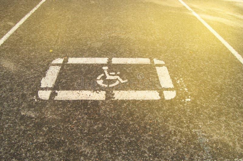 Το σημάδι στάθμευσης για τα με ειδικές ανάγκες άτομα χρωμάτισε στην άσφαλτο σε έναν κενό χώρο στάθμευσης, φως του ήλιου στοκ εικόνα με δικαίωμα ελεύθερης χρήσης