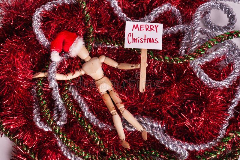 Το σημάδι στύλων Χαρούμενα Χριστούγεννας που κατέχει η ενωμένη κούκλα που βάζει βρωμίζει της κόκκινης ασημένιας γιρλάντας που φορ στοκ εικόνες