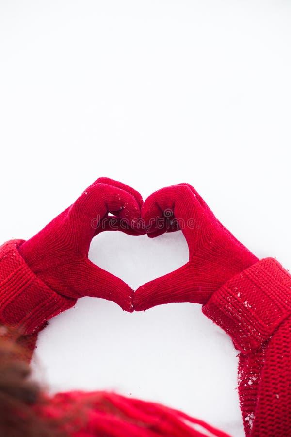 Το σημάδι καρδιών στο χιόνι παραδίδει τα κόκκινα γάντια στοκ εικόνες