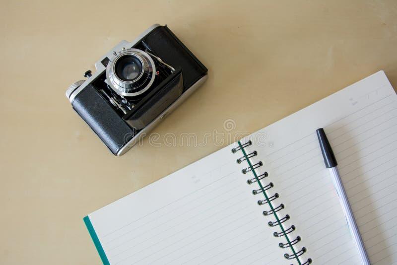 Το σημειωματάριο και η παλαιά εκλεκτής ποιότητας διπλώνοντας κάμερα ταινιών στον ξύλινο πίνακα στοκ εικόνες